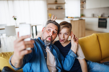 Father with small son sitting on sofa indoors, grimacing when taking selfie.