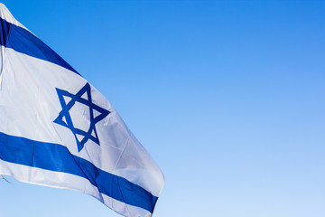 Israeli white and blue national flag with star of David evolving on a wind on empty sky background with space for copy or text, political sign and symbols concept picture