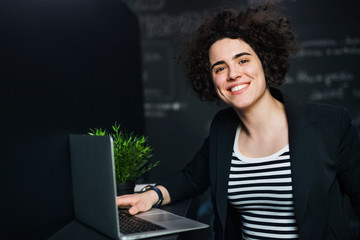 Young businesswoman with laptop in office, working.