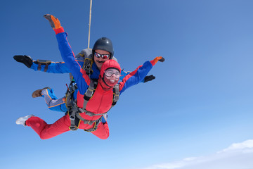 Skydiving. Tandem jump. A strong man and a young woman are falling in the sky.
