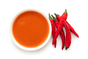 Peri peri chilli sauce in a white ceramic bowl next to a pile of red chillies isolated on white from above. Wall mural