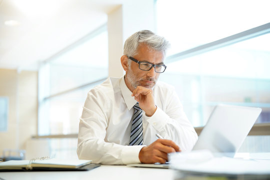 Relaxed mature businessman working in contemporary office