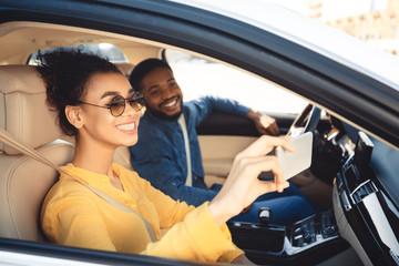 Road trip. Happy couple taking selfie in car