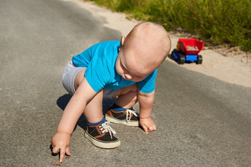 Little boy collects stones in a toy car on the pavement on a summer day