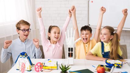 Stem education. Children raising hands after doing robots