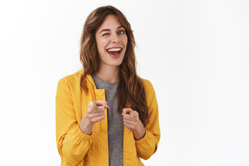 Fototapeta Gotcha. Hey wanna be friends. Cheeky confident relaxed young party girl smiling broadly winking approval pointing camera finger pistols you nice work gesture approve great choice, white background obraz