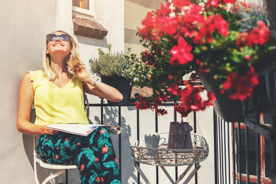 young woman enjoying the sun on romantic balcony with flower boxes
