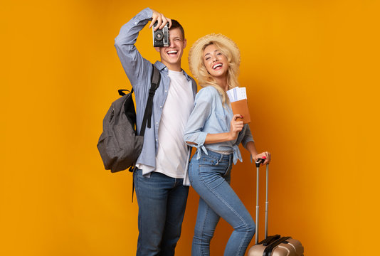 Happy couple with suitcase and tickets over yellow background