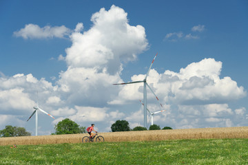 nice, active woman, riding her electric mountain bike between wheat fields and wind wheewls of a wind farm on the Swabian Alb near the city of Aalen, BadenWuerttemberg, Germany
