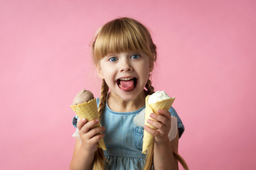little girl with pigtails in a blue dress eating ice cream in a cone on a pink background Wall mural