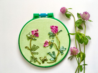 Hand embroidery with satin ribbons on a light green canvas of pink three-leaf clover flowers. Gift for St. Patrick's Day. Flat lay, copy space, close up (the embroidery made the author of photo)