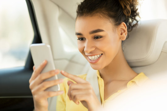 Happy woman using smartphone, sitting on back seat in car