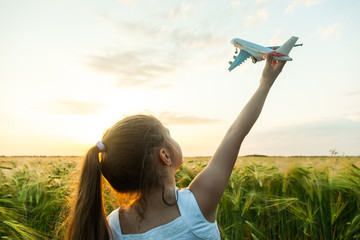 Child girl holding airplane toy during running in the field Fototapete