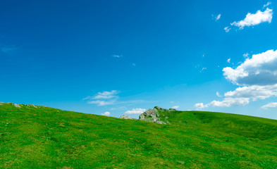 Landscape of green grass and rock hill in spring with beautiful blue sky and white clouds. Countryside or rural view. Nature background in sunny day. Fresh air environment. Stone on the mountain.
