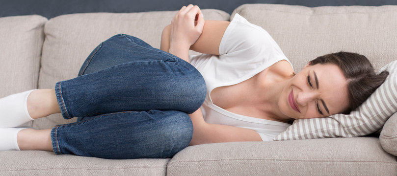 Young sad woman laying on sofa, suffering from stomach pain