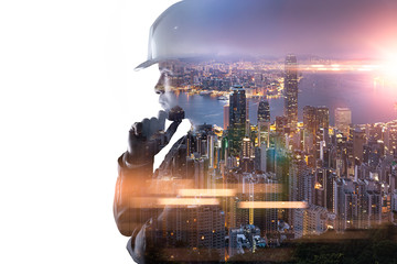 The double exposure image of the engineer thinking overlay with cityscape image and. The concept of engineering, construction, city life and future.