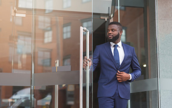 Confident african businessman walking out of modern office center