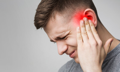 Fototapeta Young man has sore ear, suffering from otitis