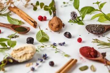 Super foods: maca powder, beetroot powder, chia and hemp, spirulina in wooden spoons on white background. Healthy eating concept.