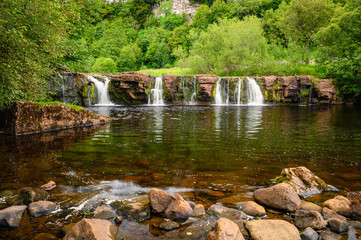 River Swale flows over Wain Wath Force, a waterfall situated on the River Swale in the Yorkshire Dales National Park and flows beneath the limestone cliffs of Cotterby Scar