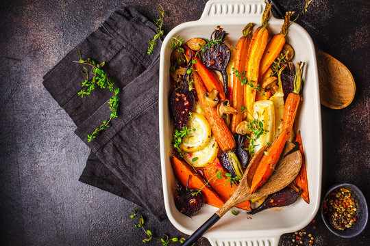 Baked vegetables with thyme in the oven dish, dark background.