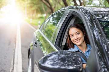 Beautiful Asian woman smiling and enjoying.driving a car on road for travel Fototapete