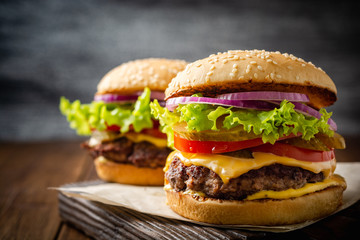 Two homemade tasty burgers on wood table. Selective focus. Wall mural
