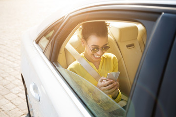 African-american girl texting on phone, sitting in car
