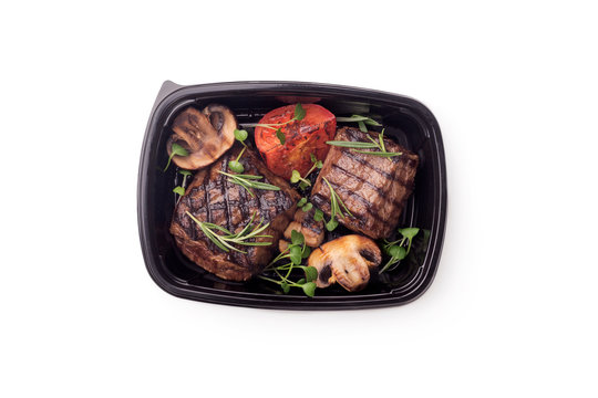 Grill cooked meat steaks with vegetables in delivery box