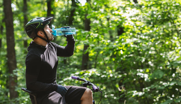 Male cyclist sitting on bike and drinking water in forest