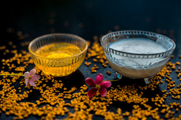 A famous natural method for dandruff on wooden surface in a glass bowl consisting of fenugreek seeds powder well-mixed with curd in a glass bowl.Along with raw curd and fenugreek seeds on the surface.