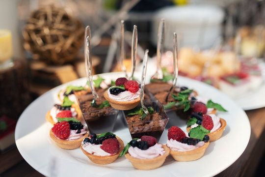 Tasty sweets on a brown rustic wooden banquet table. Summer wedding in the forest. Banquet table. Wedding candy bar. Sweet caces with raspberries, blackberries and mint