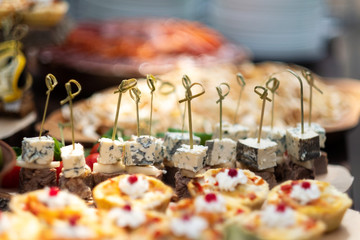 Tasty meals on a brown rustic wooden banquet table. Summer wedding in the forest