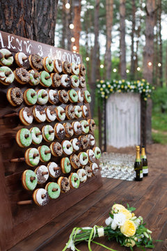 Delicious donuts on wooden stander. Wedding in the forest. Wedding decor. Donuts for guests