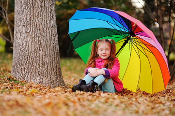 a little red-haired girl in a pink jacket sits on a background of yellow leaves with a large umbrella of rainbow color. Autumn concept