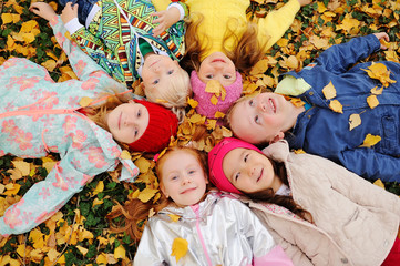 a group of children lie in the autumn yellow fallen leaves in the Park and smile.