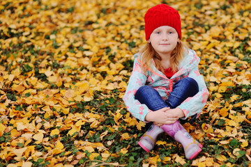 child - a little girl in a red knitted hat sitting on a background of yellow fallen autumn leaves. Space for text, copy space.