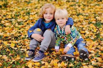 two child - little boy friends hugging against the autumn leaves in the Park.