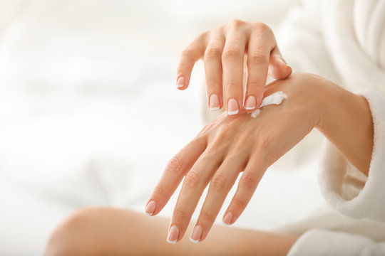 Young woman applying natural cream onto skin at home