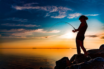 Papiers peints Peche Woman fishing on Fishing rod spinning in Norway.
