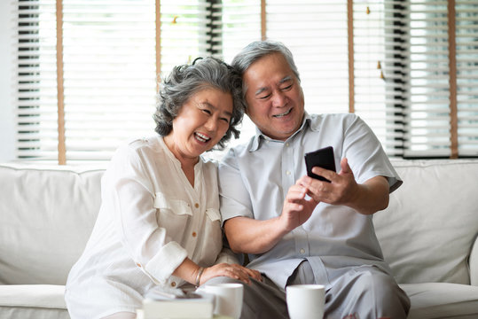 Asian senior Couple using cell phone.