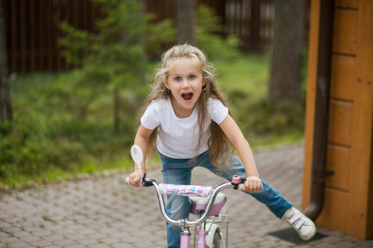 Portrait of cute little smiling girl riding bike bicycle in a courtyard on sunny summer day. Active family leisure with kids.