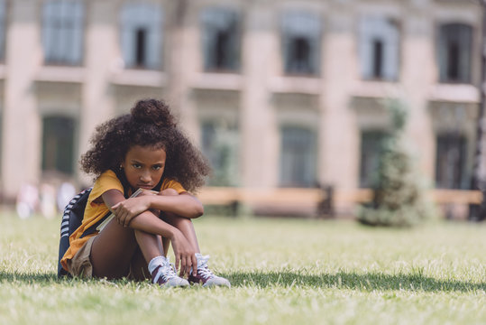 upset african american schoolgirl looking at camera while sitting on lawn