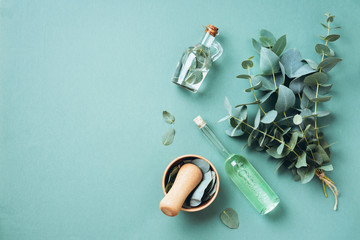 Tuinposter Apotheek Bowl, bottles of eucalyptus essential oil, mortar, bunch of fresh eucalyptus branches on green background. Natual organic ingredients for cosmetics, skin care, body treatment