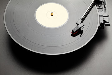 Black vinyl record player on black table background