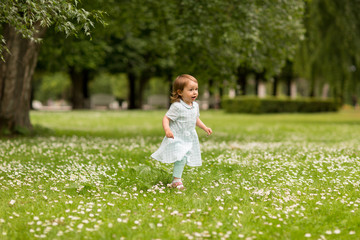 childhood, leisure and people concept - happy little baby girl running at park in summer