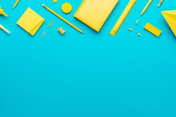 Top view photo of yellow school stationery on turquoise blue background with copy space. Flat lay...