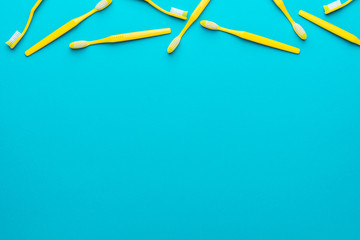Top view photo of many new yellow toothbrushes over turquoise blue background with copy space. Flat lay image of manual plastic toothbrushes with right side composition.