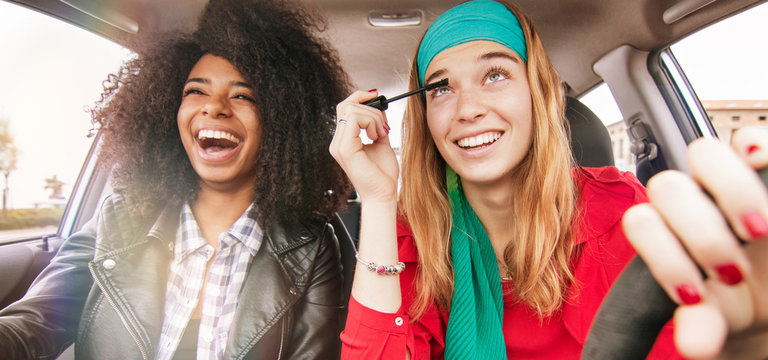fun in car girl friends driving having fun and laughing. concept of reckless driving woman doing make up while driving with afro hair girl on passenger seat