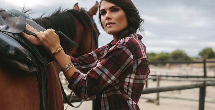 Cowgirl saddling a brown horse